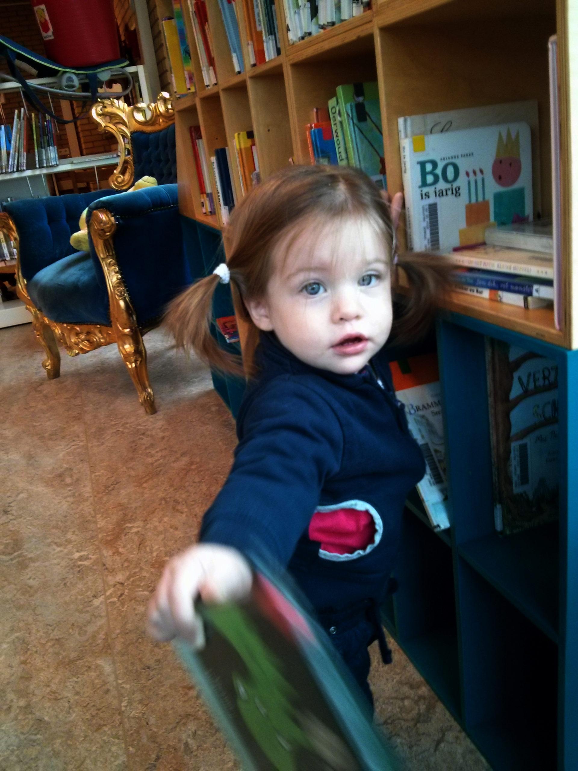 ד׳, תינוקת מתהפכת (אך עוד לא הולכת), בביקורה הראשון בספרייה.